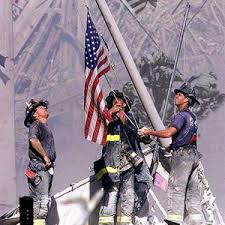 Firefighters raise U.S. flag amidst the debris of the Twin Towers.