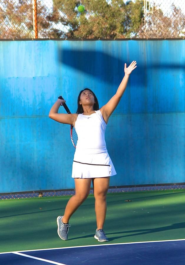 A tennis player practices a serve.