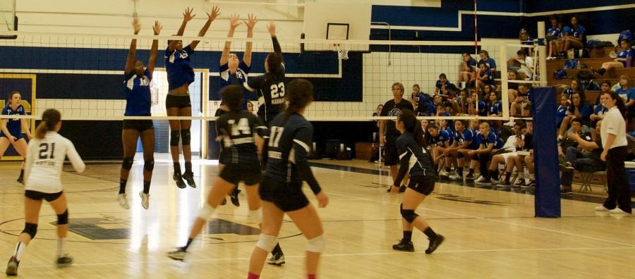 Girls' volleyball in the middle of an especially difficult play.