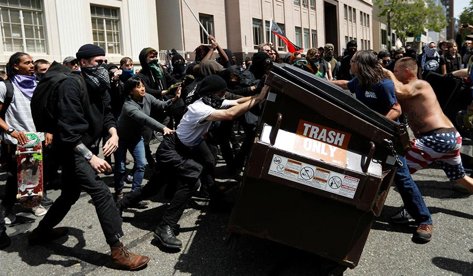Antifa rioters push down a dumpster in Berkeley, CA.