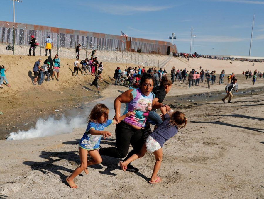 Migrant family running away from the tear gas in front of the border.