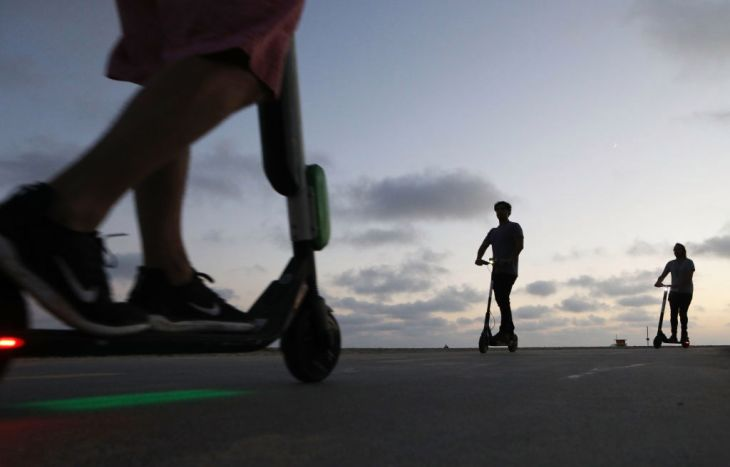 LOS ANGELES, CA - AUGUST 13:  People ride shared dockless electric scooters along Venice Beach on August 13, 2018 in Los Angeles, California. Shared e-scooter startups Bird and Lime have rapidly expanded in the city. Some city residents complain the controversial e-scooters are dangerous for pedestrians and sometimes clog sidewalks. A Los Angeles Councilmember has proposed a ban on the scooters until regulations can be worked out.  (Photo by Mario Tama/Getty Images)