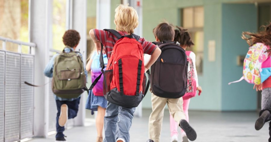 Children wearing backpacks at school