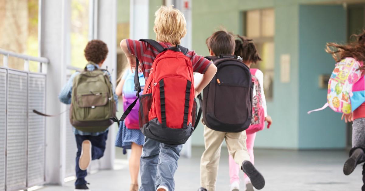 Children wearing backpacks at school
