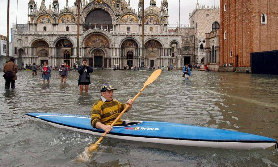 A man paddles his canoe in a flooded St. Mark's Square in Venice, Italy