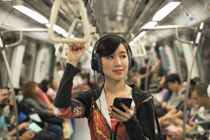 Female student jamming to her music on the subway.