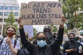 A Black Lives Matter protester holding a sign talking about the trend of the BLM movement