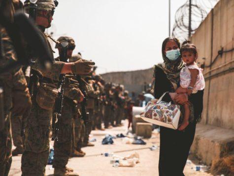 Afghanistan Woman Walking Next to American Soldiers